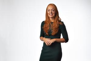 Lauren somers, with red hair and a green dress, on a white background